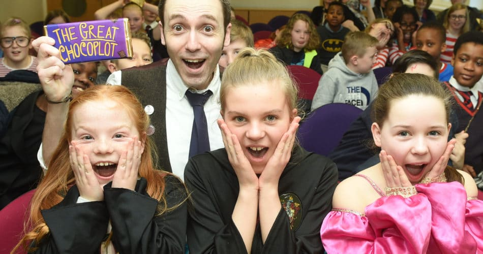 Chris Callaghan posing with children and a bar of chocolate